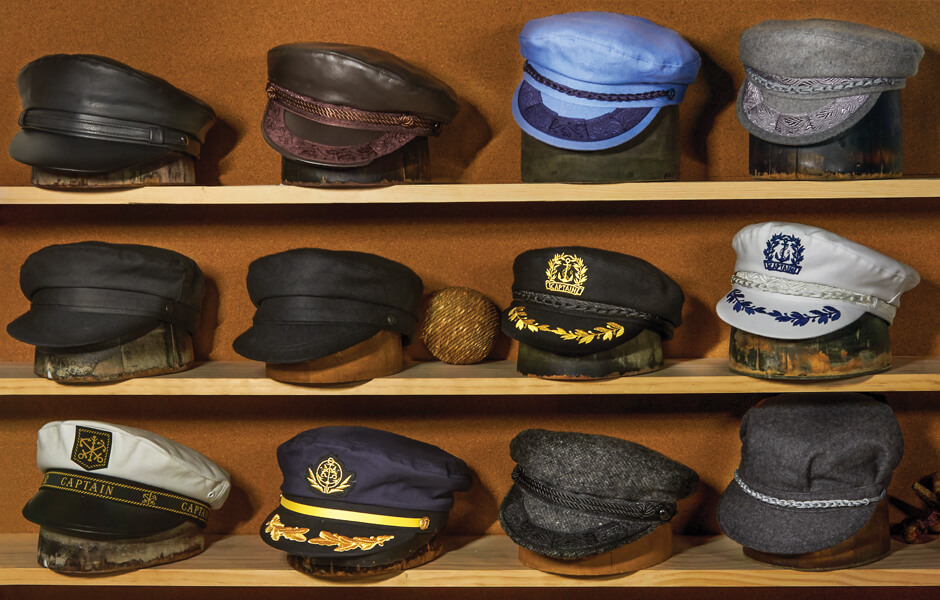 Three rows of Aegean hats displayed on hat blocks on a wooden shelf