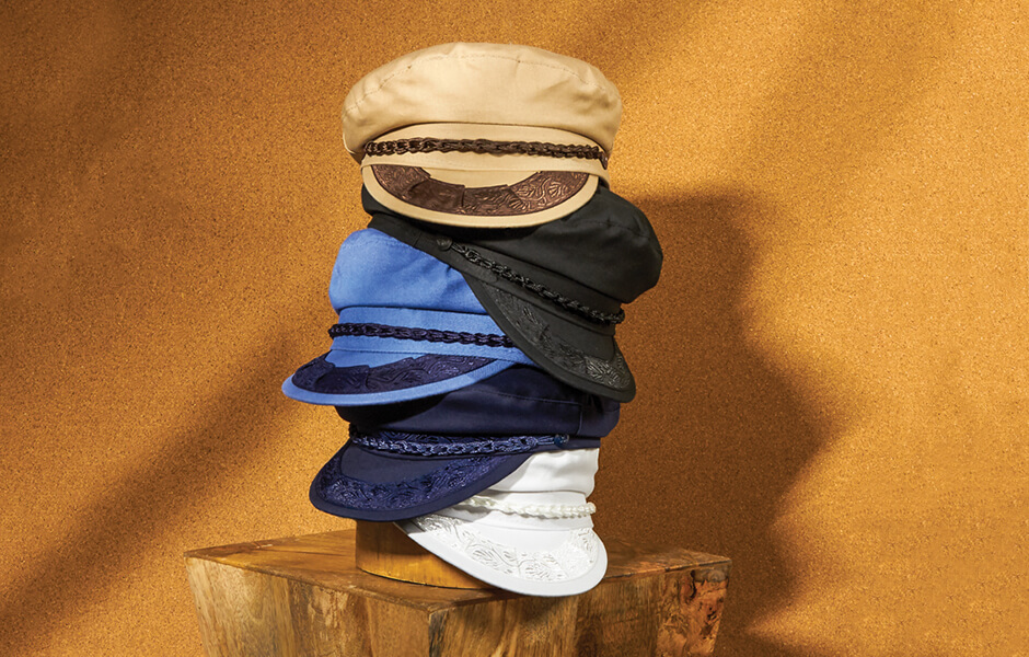 A stack of 5 Aegean hats displayed on a hat block on a wooden desk
