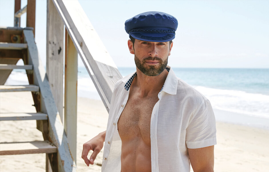 Man wearing navy blue fisherman hat and white shirt on the beach