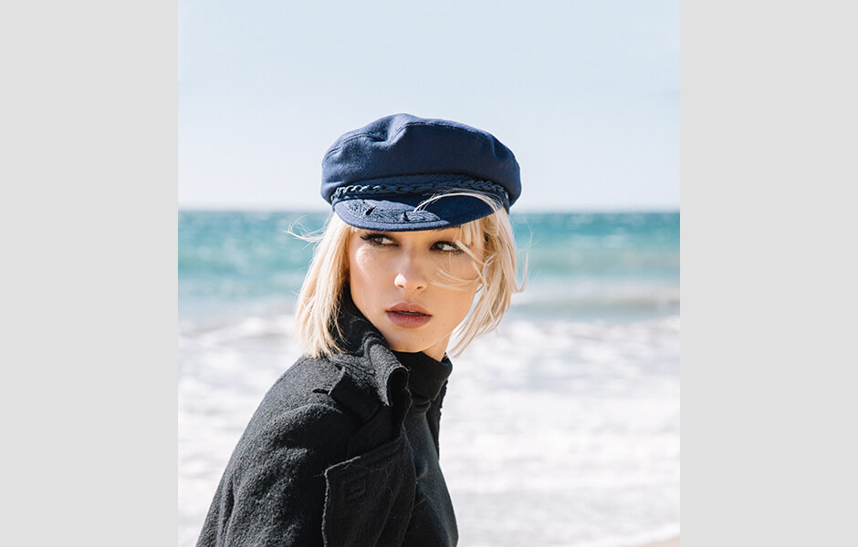 A blonde woman wearing a navy blue cap and black sweater by the beach