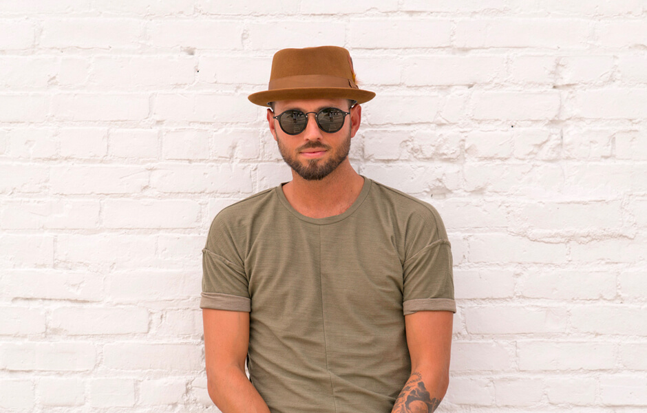 Man wearing a brown hat with arm tattoo against a white wall