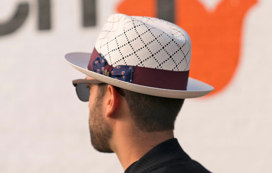Backside of man wearing a white hat and brown sunglasses