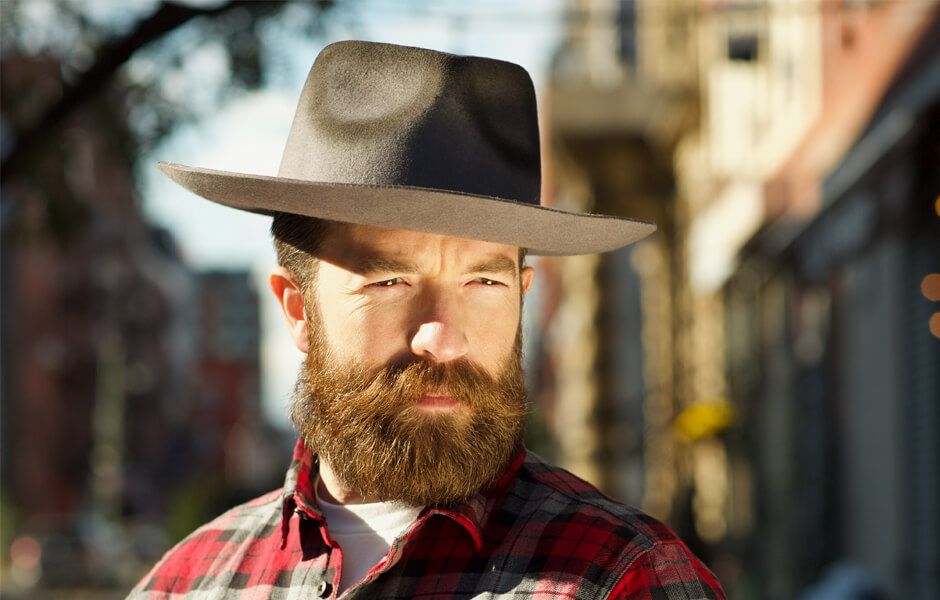 Man wearing a brown hat with a red bushy beard and red plaid shirt in the city