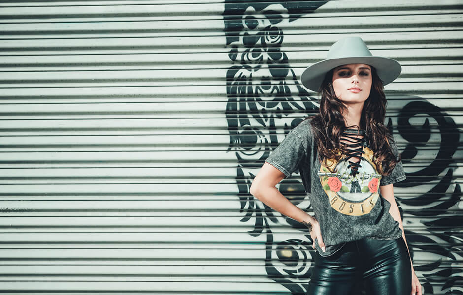 Woman wearing a gray hat and a guns and roses t-shirt standing against a garage