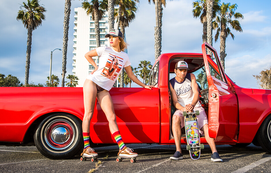 Man with a skateboard and a woman in roller skates posing against a red truck