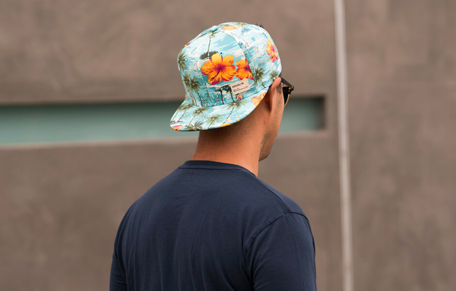 Behind shot of a man wearing a tropical blue and orange baseball cap and blue t-shirt