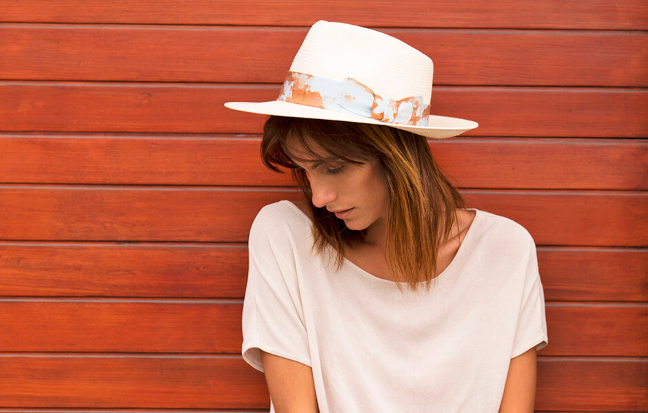 Woman wearing a white hat and t-shirt posing against an orange wooden wall