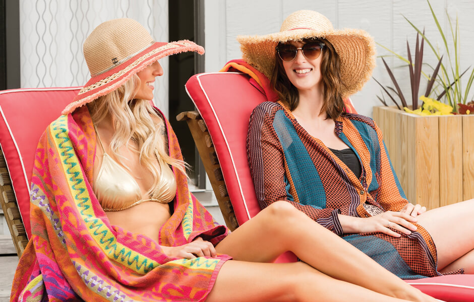 Two woman in sun hats lounging on beach chairs conversing