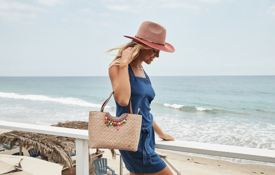 Smiling blonde woman by the beach walking with her brown and white purse with colorful ornaments