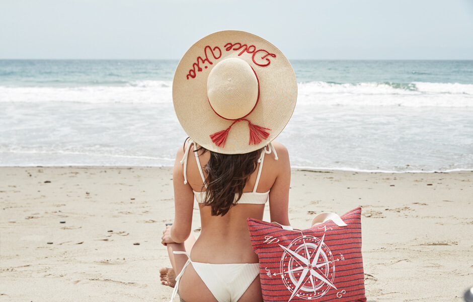 Woman in white bikini and tan sun hat with red cursive meditating on a beach with her red purse