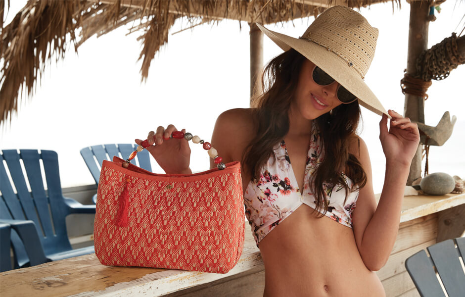 Woman wearing a white floral bikini tipping a tan sun hat and displaying her red purse