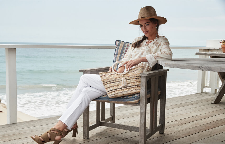 Woman resting in a wooden chair on a wood deck by the beach displaying her tan and white purse