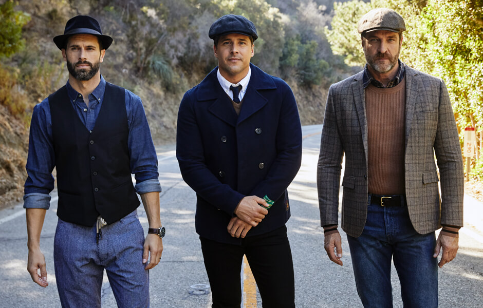 Group of men in nicely dressed clothes wearing hats while walking down a road in the mountains