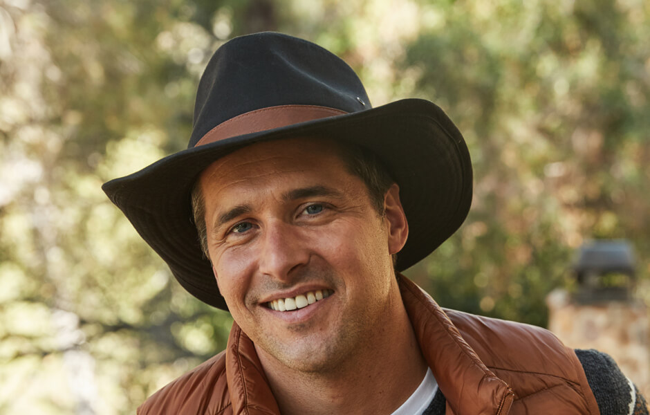 Man with a black hat with brown band smiling in a forest