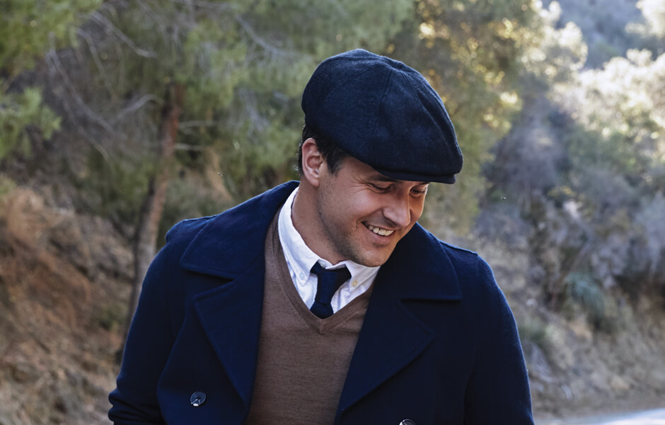 Man wearing a navy cap, tie, and jacket smiling at the ground in the forest