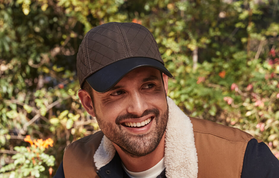 Man in brown and black cap with a heavy tan jacket smiling in a garden