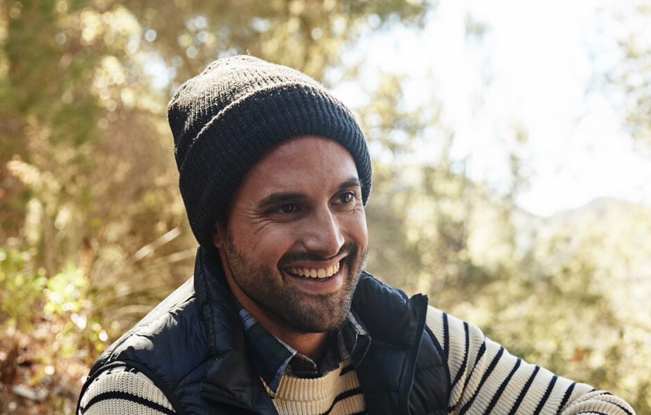 Man wearing a navy beanie and jacket smiling in the forest