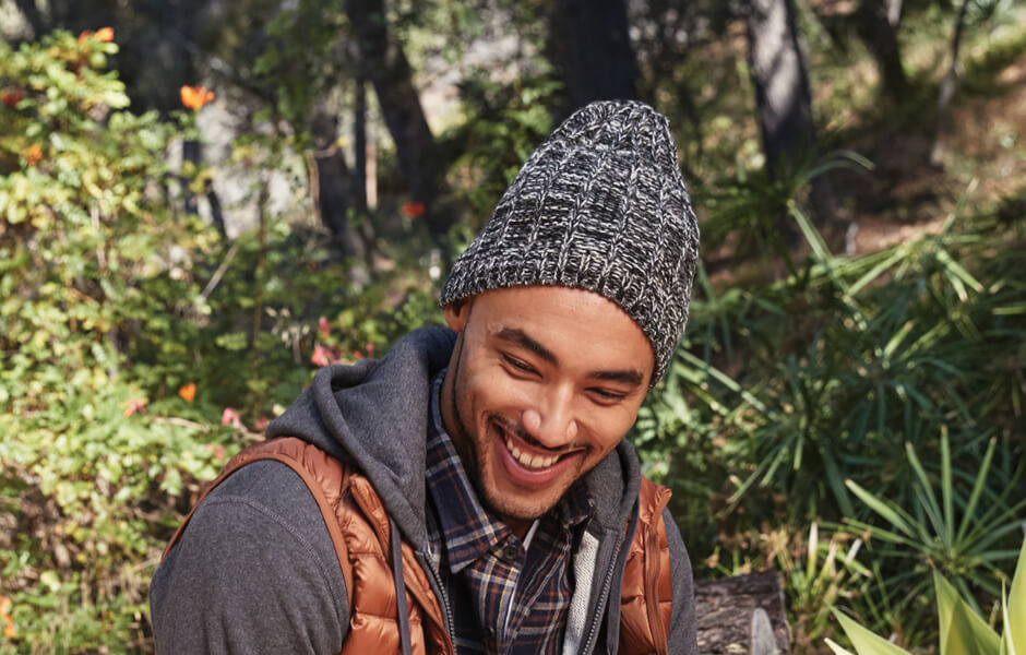 Man in a black and white beanie and heavy jacket smiling in a garden