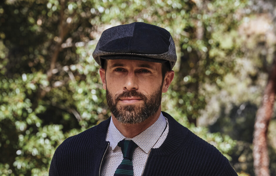 Man wearing a navy cap and sweater with shirt and tie in the forest