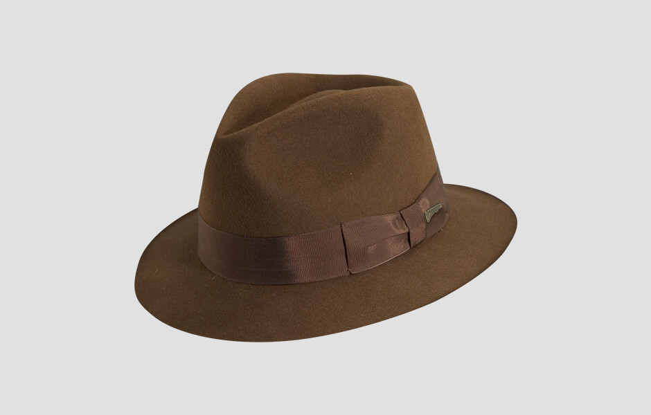 A light brown Indiana Jones hat with gold pin