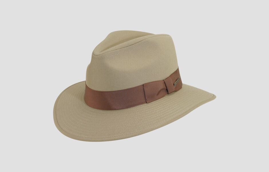 A tan Indiana Jones hat with a brown band and gold pin