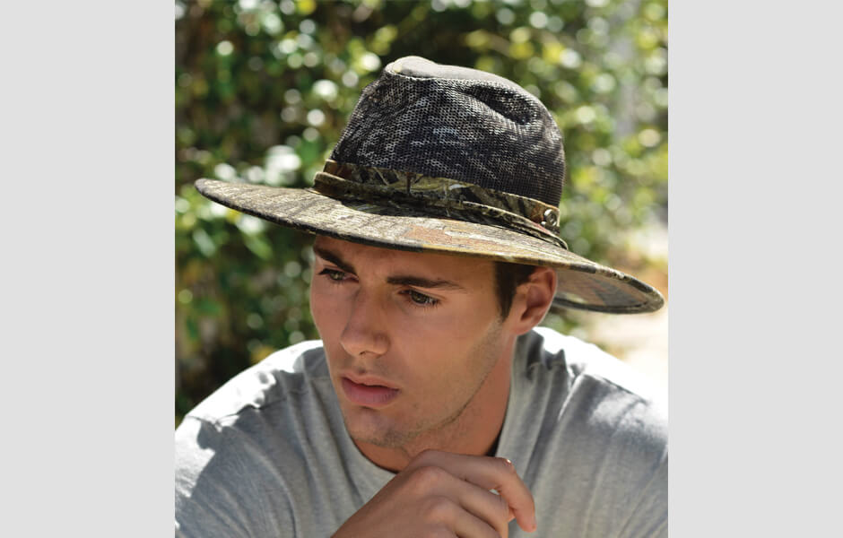 A concentrating man wearing a camouflage hat