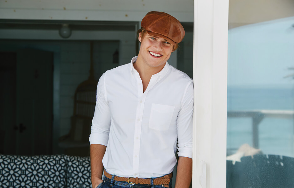 Man wearing a brown cap and white shirt smiling by a door near the ocean