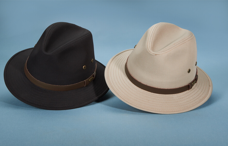 A black and tan Stetson hat against a blue background