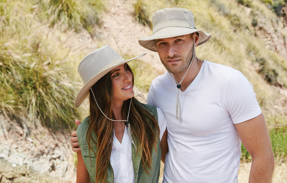 Man and woman wearing tan hats with strings near a grassy mountain