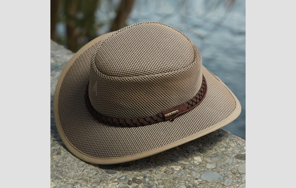 A tan Stetson hat with brown band resting on a bridge