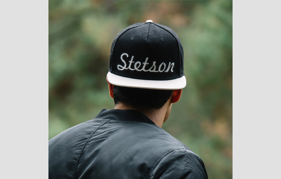 Man wearing a black Stetson hat backwards looking at the plants