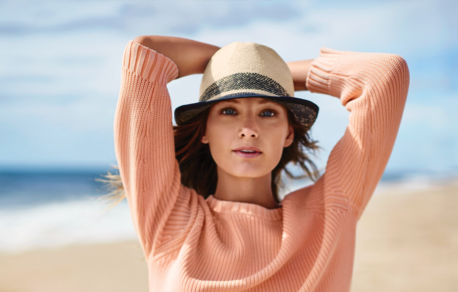 Woman wearing a tan hat with black band and pink sweater on the beach