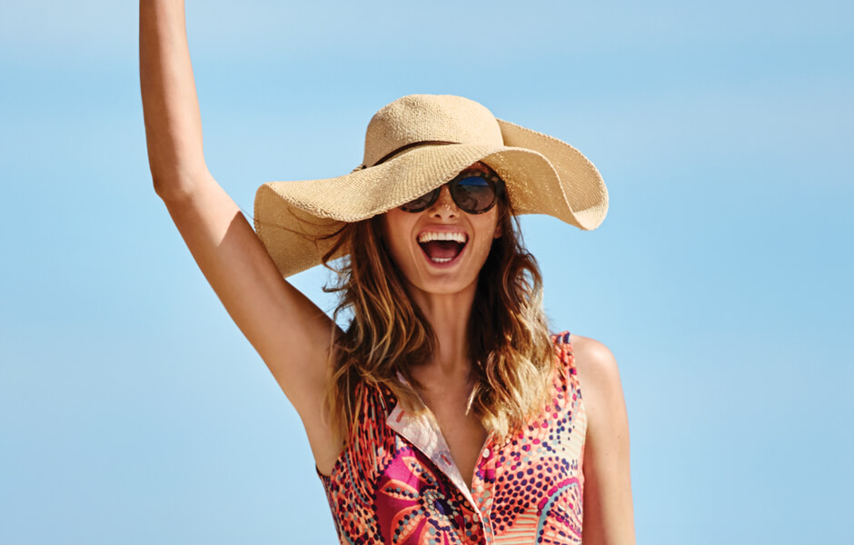 Woman wearing a big floppy tan hat with big sunglasses and a pink dress on the beach