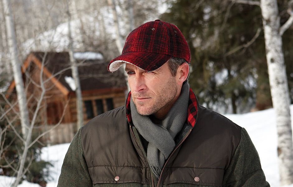 Man wearing a red plaid ball cap, coat, and scarf in the snow near a wood cabin