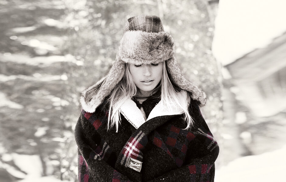 Woman wearing a tall fur hat and plaid blanket in the snow