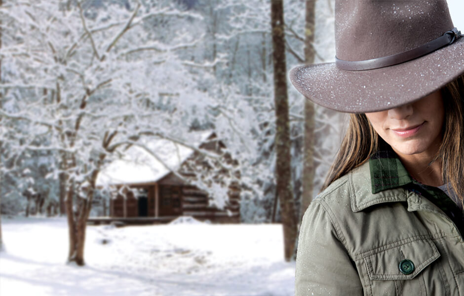 Woman wearing a brown hat and green jacket smiling near a wood cabin in the snow