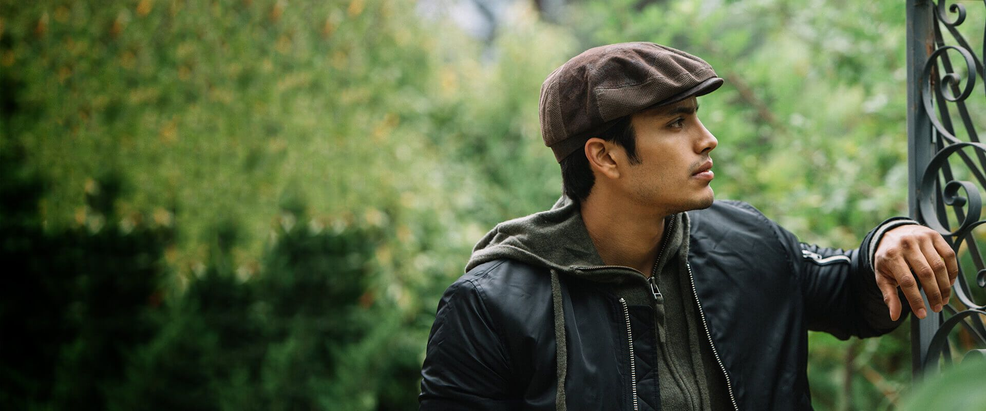 Man wearing a brown cap and a black leather jacket in the forest