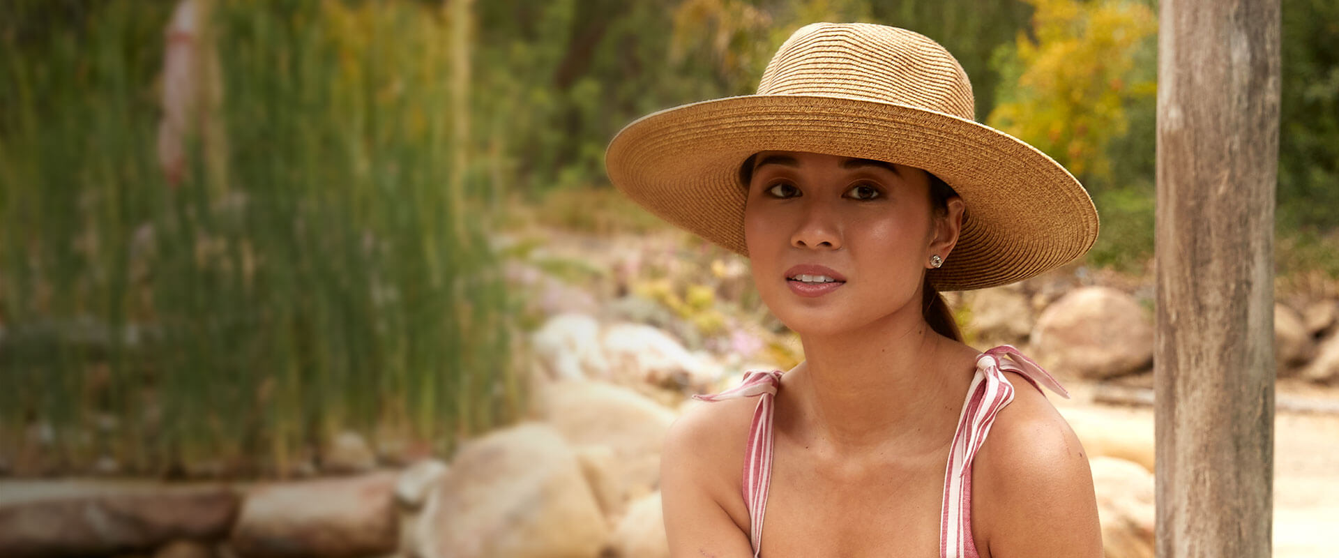 Woman wearing a tan hat in a pink dress by a creek